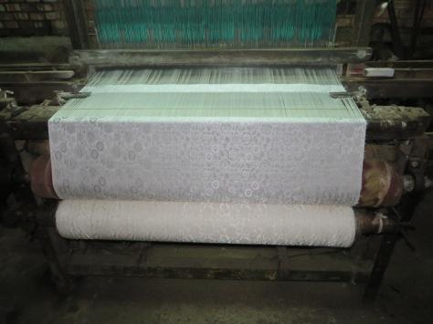 Il y a de nombreuses machines à tisser la soie comme celle-ci dans l'atelier.